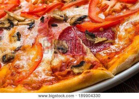 Delicious pizza with mushrooms, peppers, bacon and salami closeup