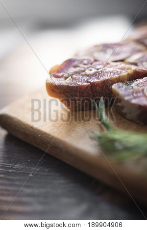 Slice of red smoked salmon fish and fresh green dill on a light wooden cutting board on a dark wooden background