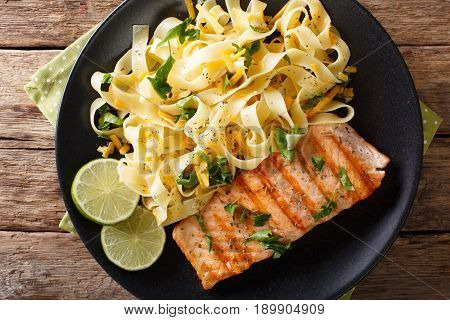 Pasta Fetuccini With Cheese Cheddar And Grilled Salmon With Herbs On A Plate Close-up. Horizontal To