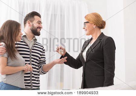 Couple renting a new flat. Smiling man and woman receiving keys from an estate agent. Moving to new rented flat.
