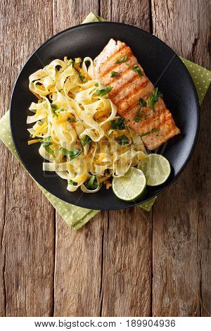 Pasta Fetuccini With Cheddar Cheese And Grilled Salmon On A Plate Close-up. Vertical Top View