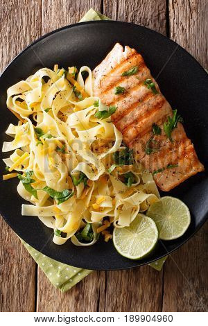 Pasta Fetuccini With Cheese Cheddar And Grilled Salmon With Herbs On A Plate Close-up. Vertical Top