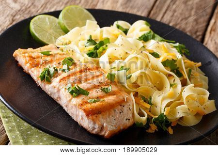 Grilled Salmon Fillet With Homemade Fetuccine Pasta Closeup. Horizontal
