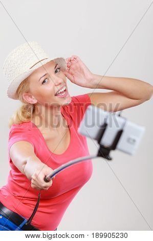 Technology modern photography confidence conept. Happy attractive adult blonde woman with sun hat taking picture of herself with smartphone on selfie stick.