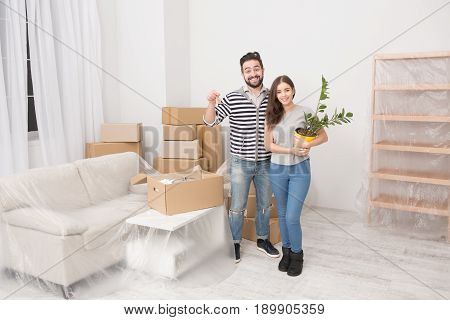Young couple moving to new apartment. Happily smiling man and woman just moved to a new home. Man keeping keys in one hand and woman keeping indoor plant.