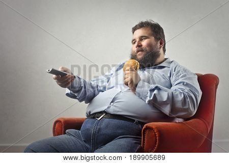 Fat man sitting in a red armchair, eating a hamburger while watching tv
