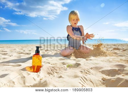 Closeup On Sunscreen Bottle And Child Playing In Background