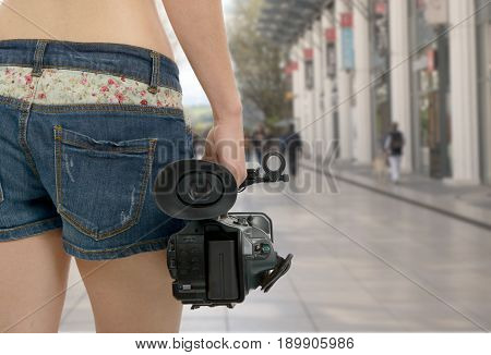 a cameraman girl holding his professional camcorder in the street
