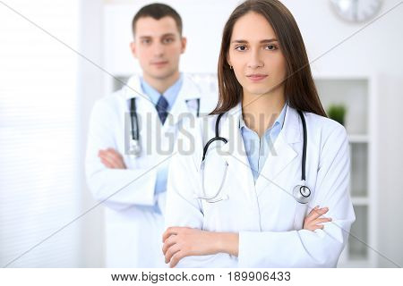 Friendly female doctor on the background of a male physician in hospital office. Ready to examine and help patients. High level and quality medical service concept. Best treatment and patient care concept