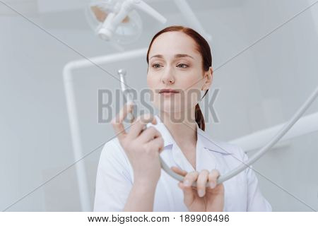 My job. Serious young dentist holding instrument in both hands and looking attentively at it while being ready for work
