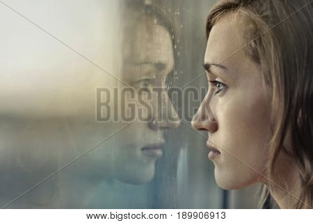 Sad girl standing in front of a window in a rainy day