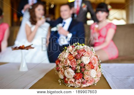 Pink and red wedding bouquet lies on the table in the front of newlyweds sitting on the coat