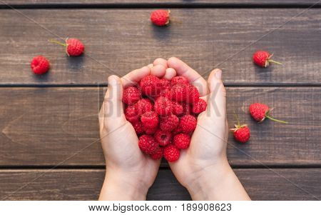 Handful of fresh raspberries in woman's hands on brown rustic wood background. Harvest of healthy food concept. Natural ripe organic berries on wooden table, top view.