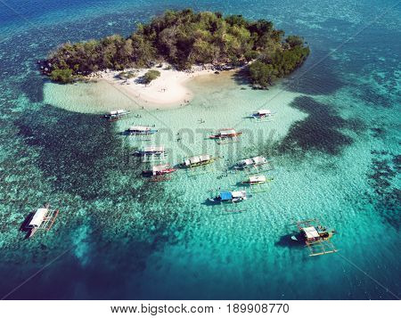 Aerial view of tropical island  with boats surrounded by turquoise sea. Palawan