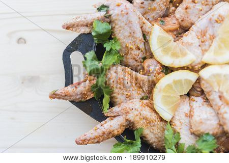 Fresh chicken wings in spices and granulated mustard green parsley and lemon slices lie in a black frying pan on a light wooden background.