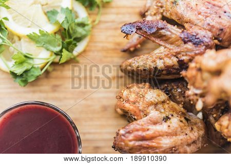 Grilled chicken wings red sauce lemon slices and green parsley leaves lie on a light bamboo cutting board.