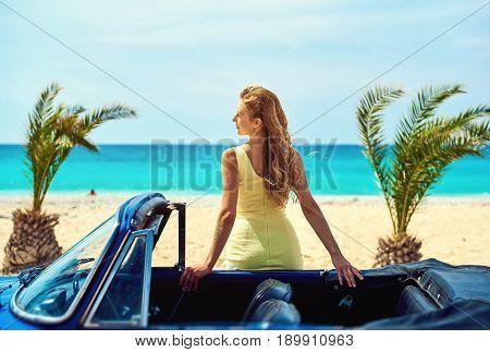 Attractive woman near retro car on the tropical beach near turquoise sea. Idyllic scenery