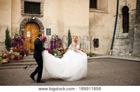Bride Looks Over Her Shoulder On A Groom Who Holds Her Wedding Dress