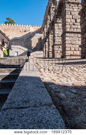 Partial view of the Roman aqueduct and stairs to access the wall surrounding the city located in the city of Segovia Unesco World Heritage Site Spain