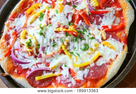 Overhead of pizza with salami onion yellow and red bell peppers and mozzarella cheese