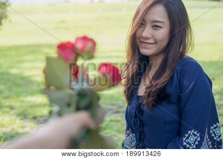 A man giving red rose flowers to asian girlfriend on Valentine's day with green grass background
