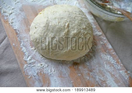 Ball of dough on a cutting board with napkin and mixing bowl