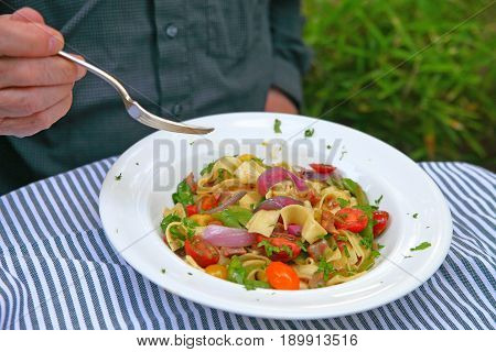 A man eating a meal of noodles with onions cherry tomatoes and fresh peas on a striped gray and white cloth