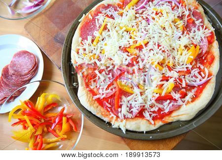 Pizza ready for the oven with dishes of ingredients alongside