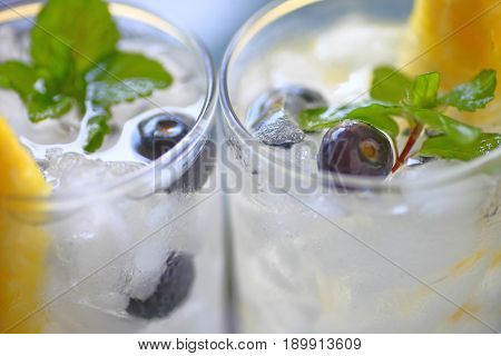 Two wine cocktails with fresh blueberries pineapple and mint in natural light