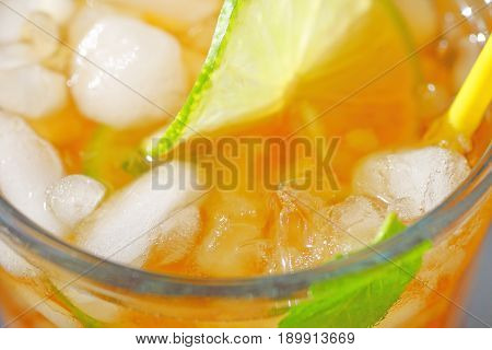 Overhead of glass of iced tea with mint lime and a straw