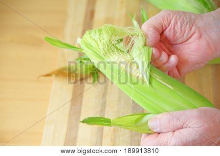 A man pulls the husk from an ear of corn over a cutting board