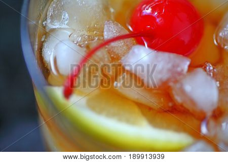 Overhead of whiskey sour over crushed ice with lemon and cherry