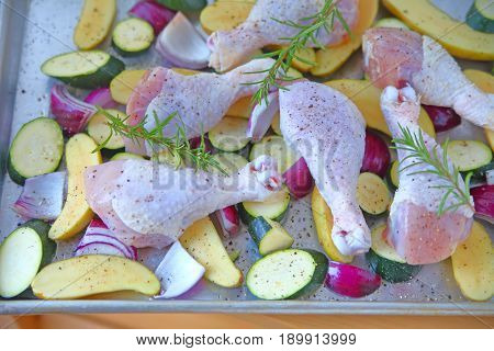 Baking pan with raw chicken legs zucchini red onion and fingerling potatoes seasoned and ready to bake