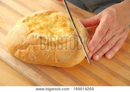 A man begins to cut slices from a loaf of artisan cheese bread