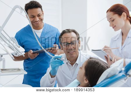 They are interns. Attentive man working as dentist being at his cabinet while treating teeth of his little patient