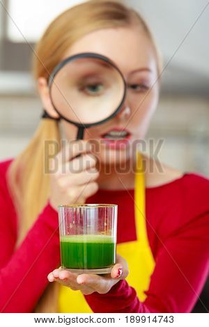Woman Looking At Vegetable Juice Through Magnifying Glass