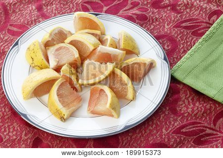 Many pieces of red grapefruit on a white round plate placed on a red placemat near a green cloth napkin. Red grapefruit cut into pieces on a dish ready to eat.