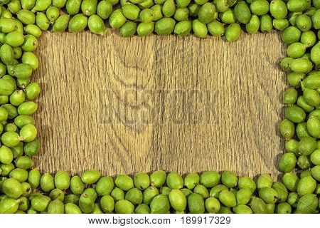 Picture frame made of green young walnuts in husks on wooden table