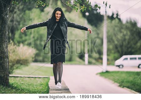 Young Pretty White Girl With Black Long Hair In Black Clothes Walks Along The Curb And Balances Her