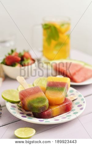 Homemade natural ice pops in a ceramic plate next to pieces of fruit, such as strawberries or watermelon, on a rustic pink table