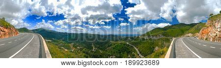 Panoramic view on car road highway spiral green hills mountains romantic blue sky clouds. Spain holidays vacation tours trip car travel. Green fields green mountains hills. Sea view