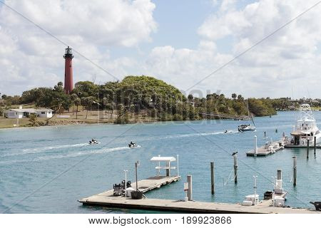 Jupiter FL USA - March 30 2017: Boat docks and people on jet skis boats and paddle boards in the Loxahatchee River. People on watercraft on Jupiter Inlet near a lighthouse.