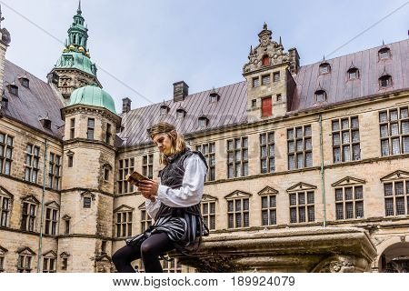 Actor performing prince Hamlet and reads a book at Kronborg Castle Elsinor Denmark May 26 2017
