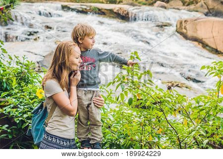 Mother And Son On The Background Of Beautiful Camly Waterfall In Da Lat City