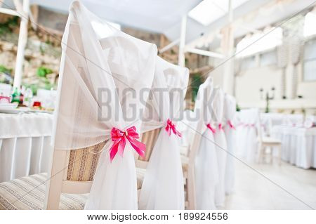 Wedding Guest Chairs With Pink Ribbons At Wedding Hall.