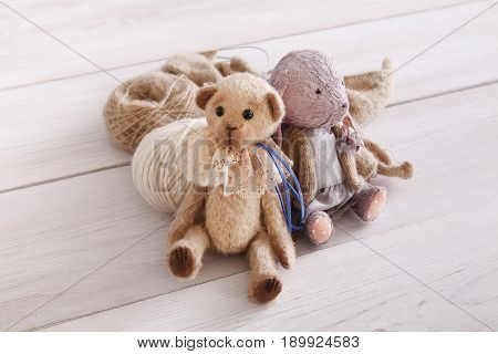 Vintage handmade toys with wool close up. Plush rabbit and teddy bear with materials of it, copy space. Creativity, handicraft, hobby concept
