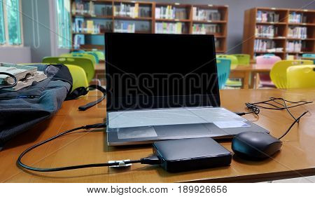 External or portable hard drive (HDD) connected to laptop computer for transfer or backup data on wooden texture office desktop,Blank laptop screen in library.