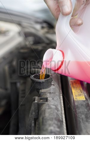 The mechanic pours the cooling fluid into the radiator spure. Car service. Adding liquid to the car's radiator.