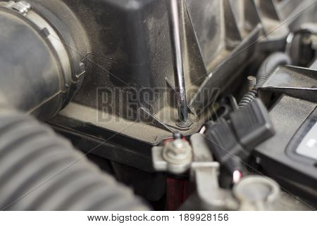 Unscrew the screw from the air filter cover with a screwdriver.