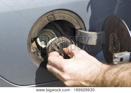 The man unscrews the fuel filler cap in the car. A male hand opens the fuel fill in the car